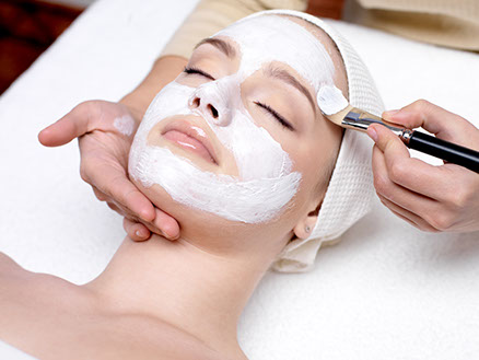 Beautiful young girl with facial mask at beauty salon